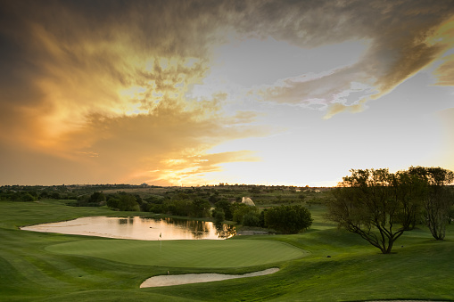 Panoramic view of water hazards on a fairway golf course at sunset