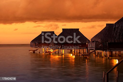 Tropical Tahiti bungalows at sunset