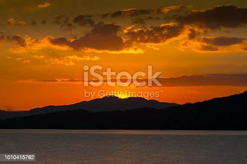 A water in dam reflecting sunset above mountain with cloudy sky located at north east of Thailand