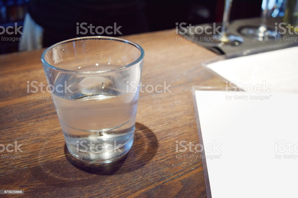 Water in glass on a table with blank menu for copywriting space stock photo