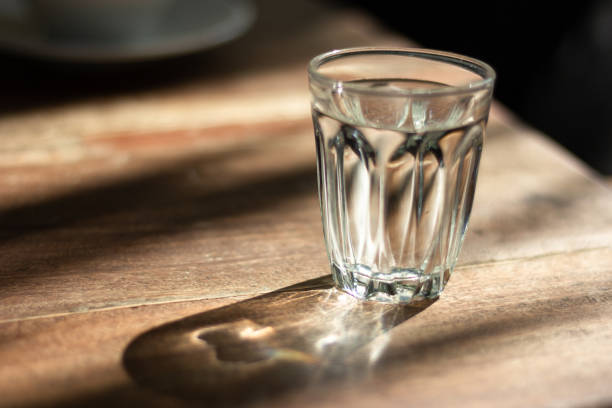シャドウ、朝の日差しの木製テーブルの上のガラスの水します。 - グラス ストックフォトと画像