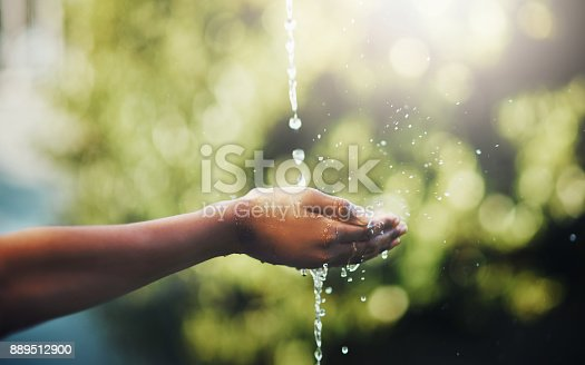 Cropped shot of hands held out to catch a stream of water outside