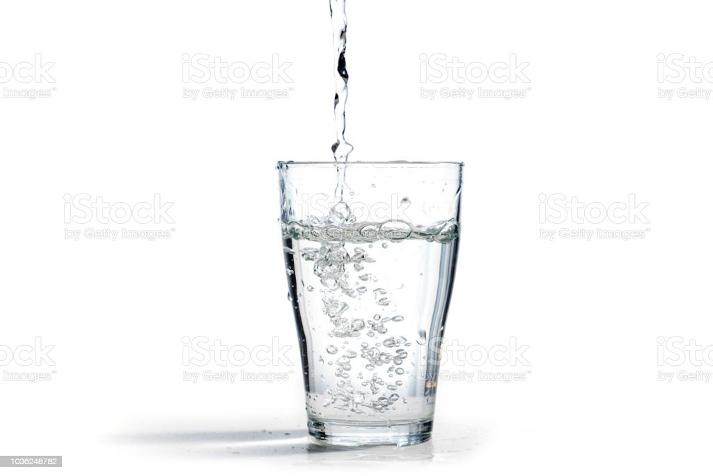 water is poured into a drinking glass, isolated on a white background with copy space royalty-free stock photo
