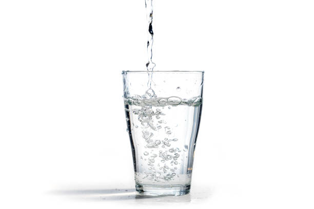 water is poured into a drinking glass, isolated on a white background with copy space - glass stock photos and pictures