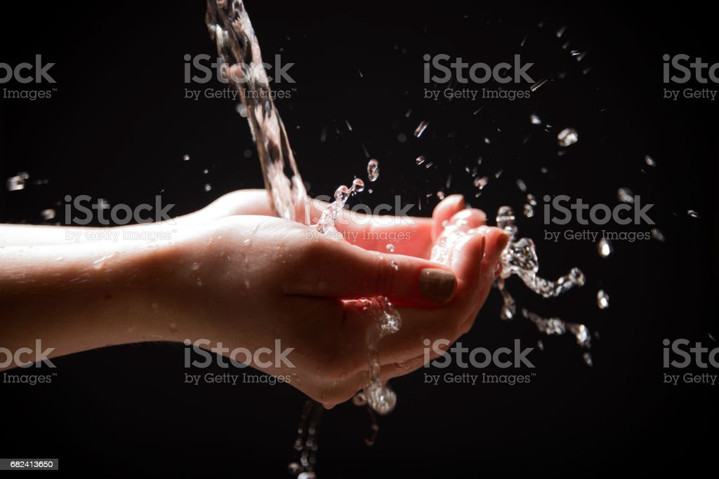 Water is poured into the palms of the hands, splashes from the palms royalty-free stock photo