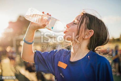Little girl is taking a big gulp of water from a bottle during athletics club.