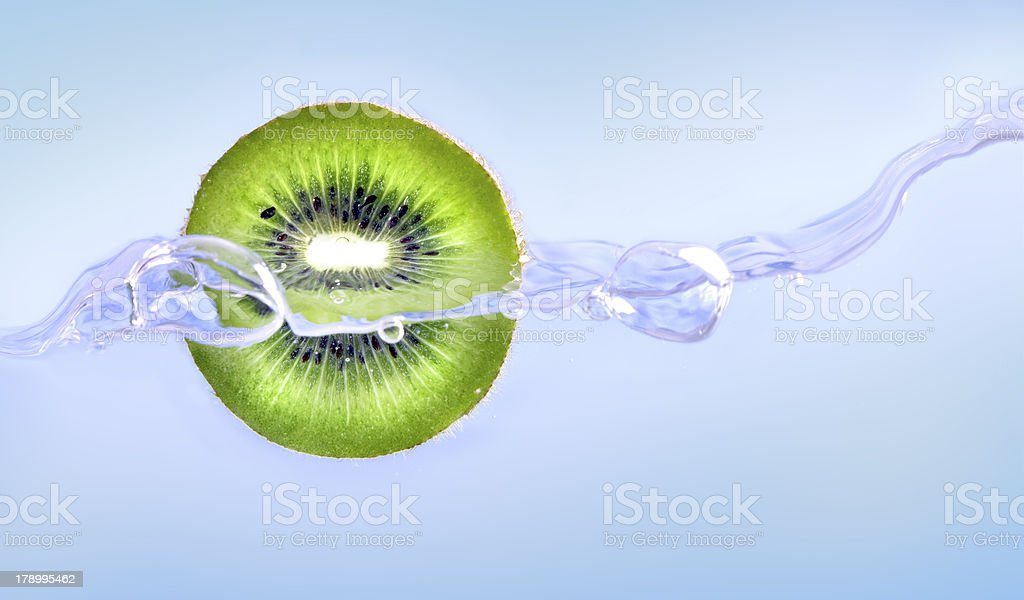 Water jet around kiwi on blue background royalty-free stock photo