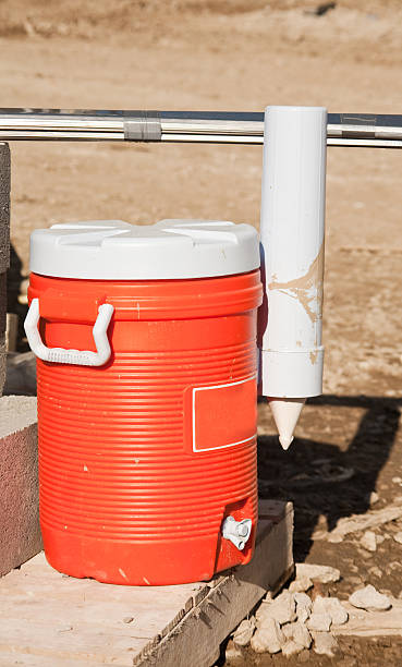 water jug, orange plastic an orange plastick water jug sits in the morning sun at the construction site cooler container stock pictures, royalty-free photos & images