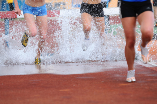 Runners at water jump during steeplechase event, low section