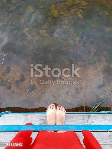 Water lake view pier bridge tanned legs with red pedicure red dress