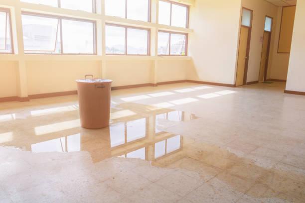 從天花板上的紅色水桶漏水滴落內部辦公樓, 在水磨石地板上流動 - 大廈樓層 個照片及圖片檔