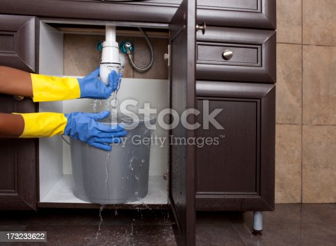 Woman hands trying fix water sink leakage by closing plastic siphon waste trap.