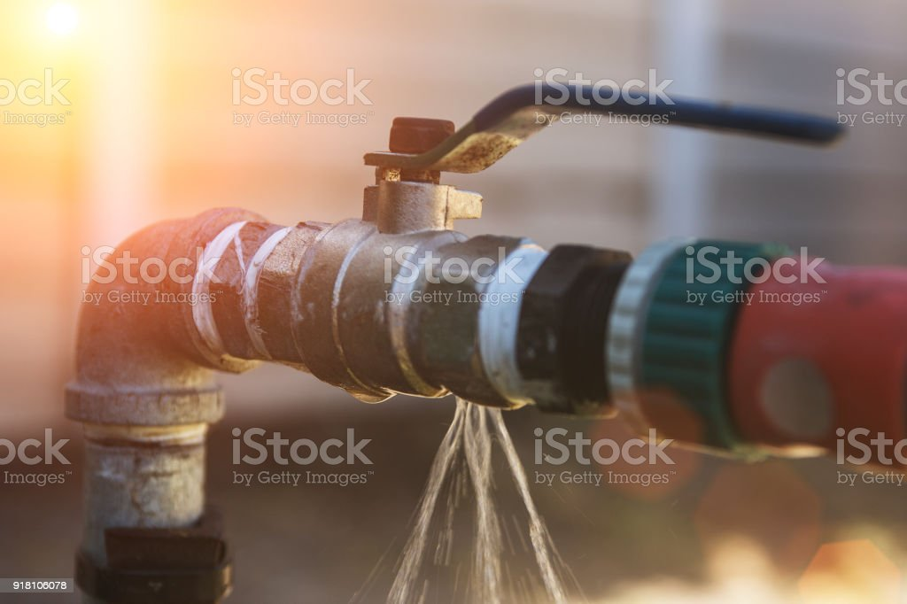 Water leaking from a irrigation pipe faucet stock photo