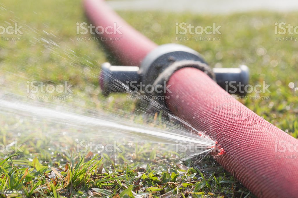 water leaking from hole in a hose water leaking from hole in a hose Agriculture Stock Photo