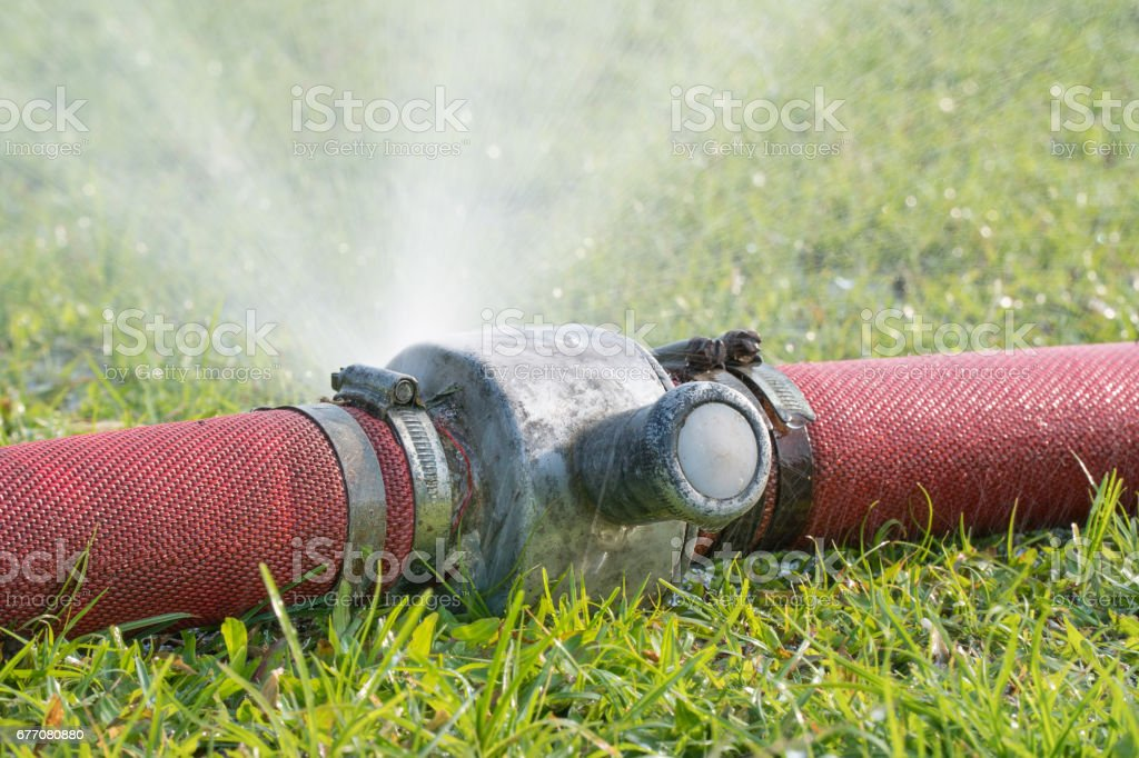 water leaking from hole in a industrial hose. stock photo