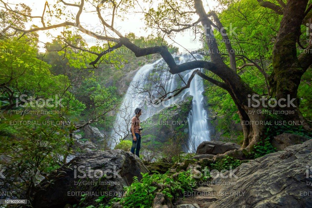 Water man watching a beautiful waterfall. Khlong Lan Waterfall National Park in Thailand stock photo