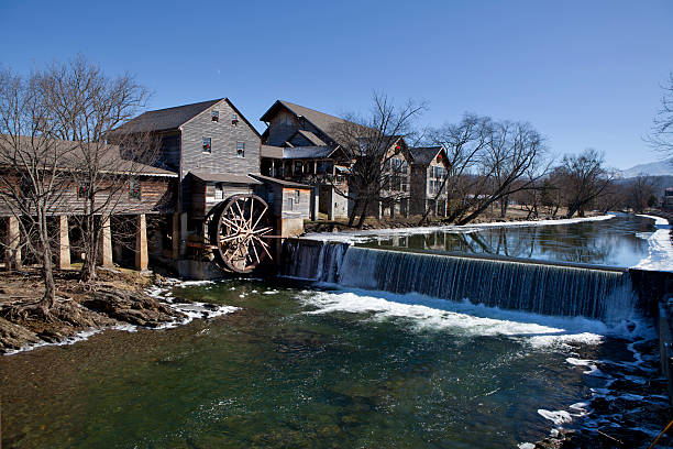 Water Mill in Pigeon Forge, Tennessee Watermill on the Little Pigeon river, in the mountain community of Pigeon Forge, Tennessee during the winter. Ice can be seen along the banks of the river pigeon forge stock pictures, royalty-free photos & images