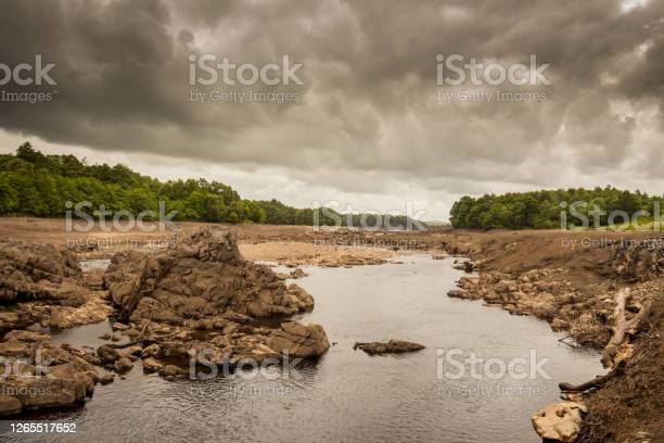 Photo of Water of Ken flowing out of a gorge on a drained or dewatered Earlstoun Dam