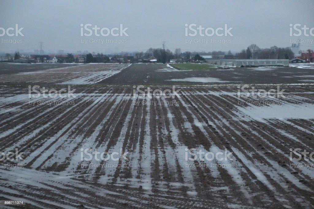 Water op de velden van de boerderij na de oogst met smeltende sneeuw foto