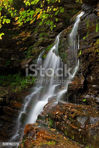 Wilderness waterfall cascades and plunges over rocky ledges in early Autumn.