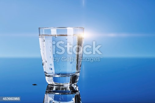 glass of drinking water on a blue table
