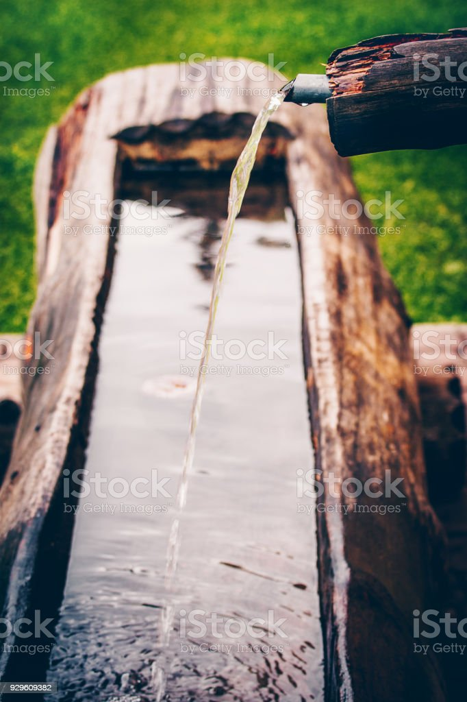 Water pipe with fresh water streaming into the wooden washtub. Typical for Switzerland countryside and hiking regions. stock photo