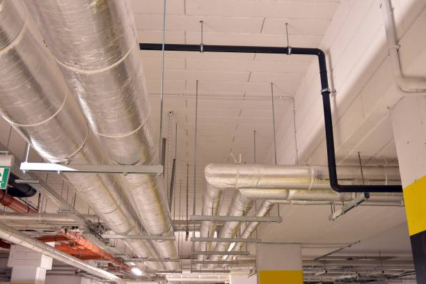 Water pipes and cable trays run under ceiling of a building stock photo