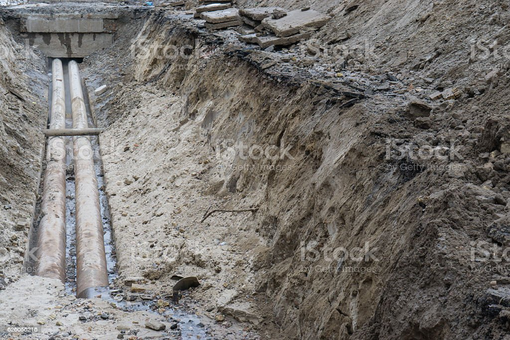 water pipes in ground during plumbing construction site pit trench stock photo