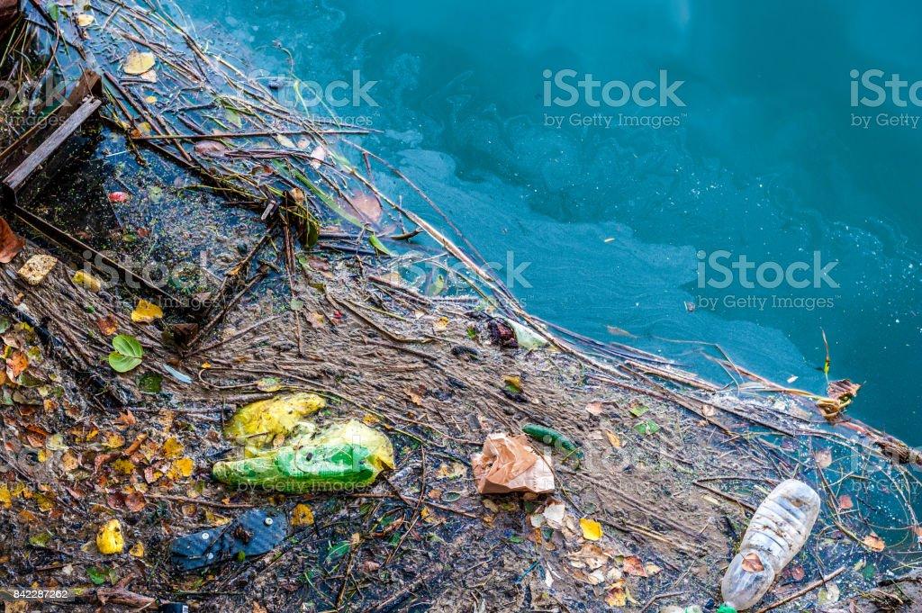 Agua contaminación basura vieja y parches de aceite en la superficie del río - foto de stock