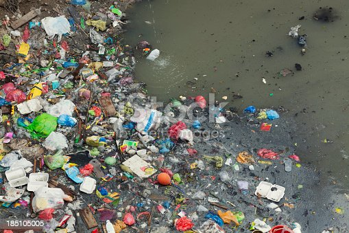 Lots of garbage floating on a small river near the sea.