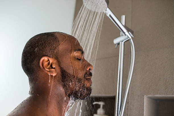 Water pouring down a man's face under a shower stock photo