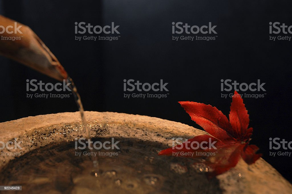 Water pouring from bamboo spout into stone fountain royalty-free stock photo