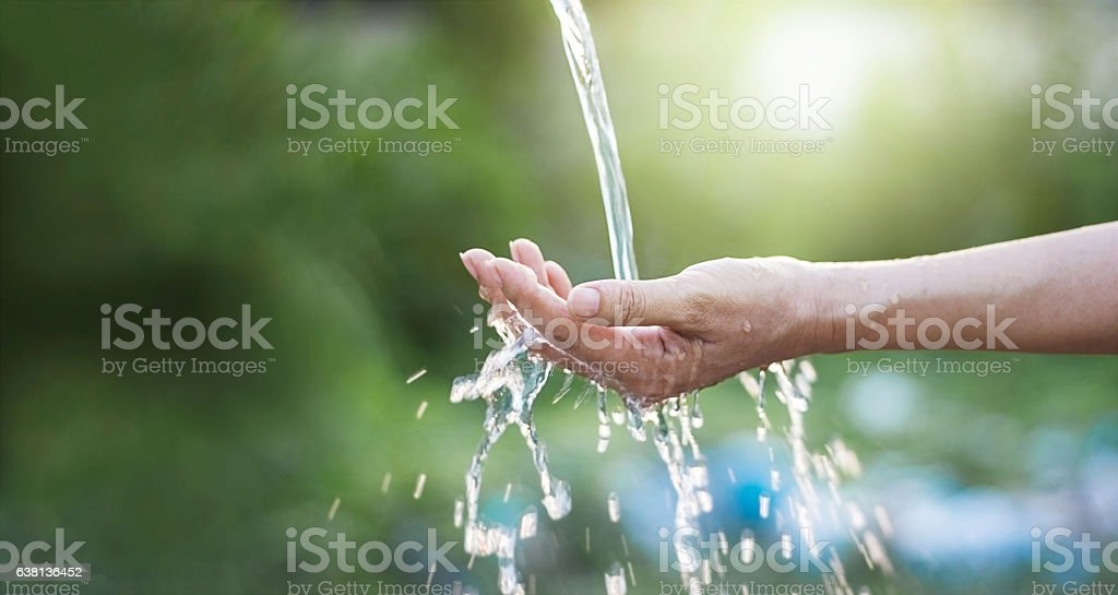Water pouring in woman hand on nature background stock photo