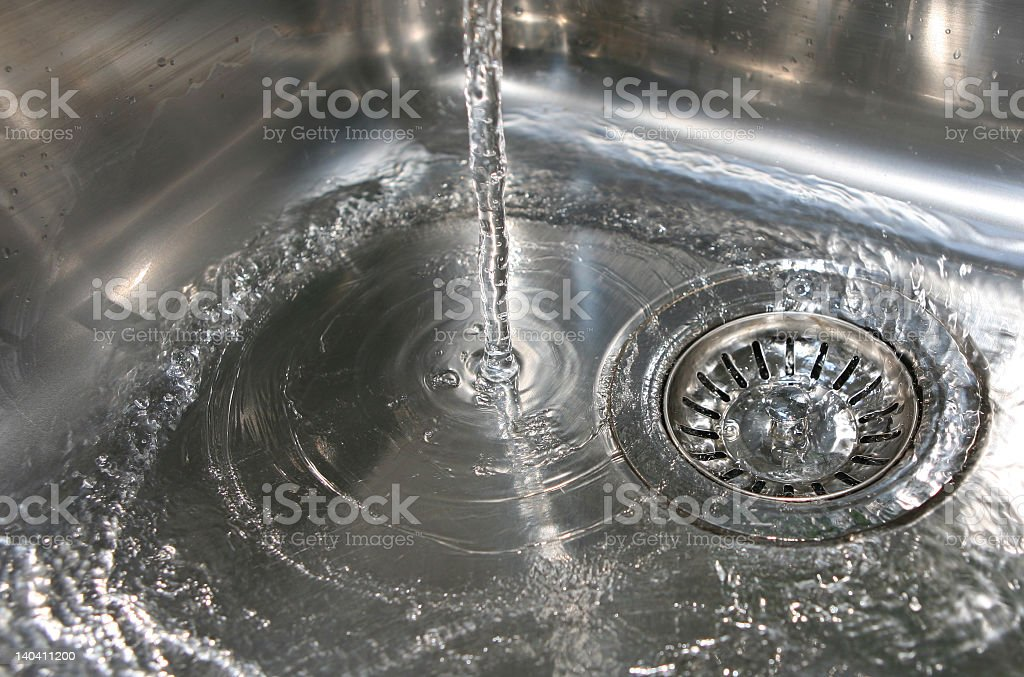 Water pouring into a silver sink and draining down the drain royalty-free stock photo