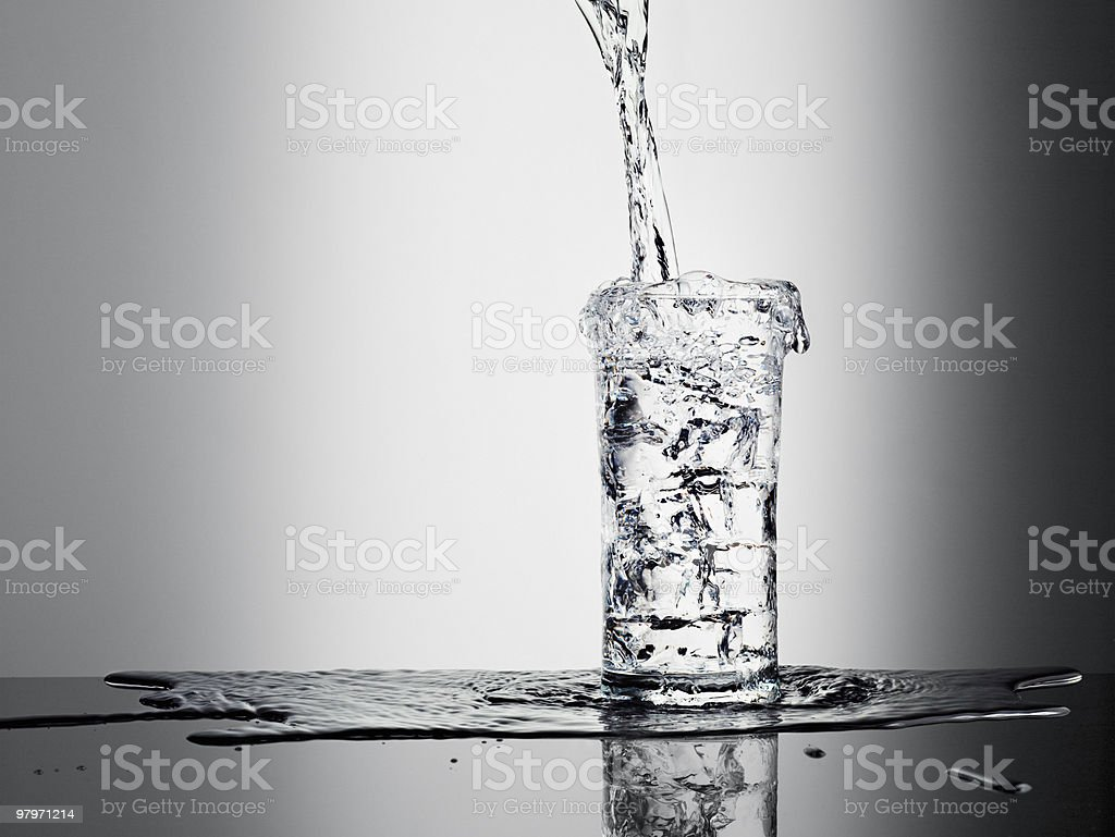 Water pouring into glass and overflowing stock photo