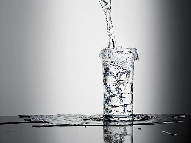 water pouring into glass and overflowing - overflowing stock photos and pictures