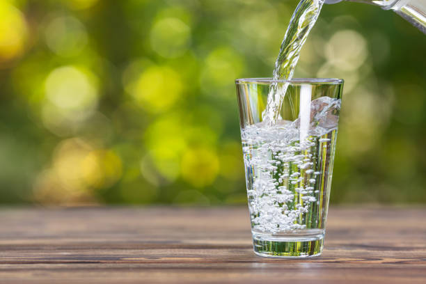 water pouring into glass water from jug pouring into glass on wooden table outdoors water stock pictures, royalty-free photos & images