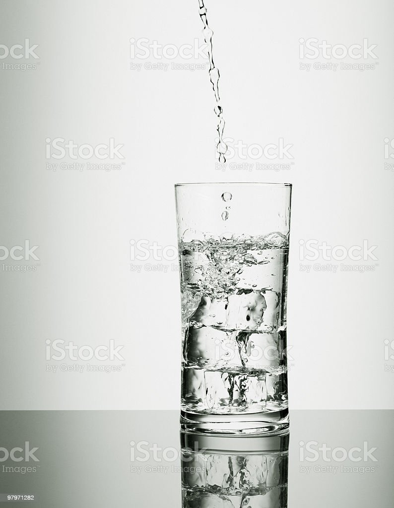 Water pouring into glass with ice cubes royalty-free stock photo