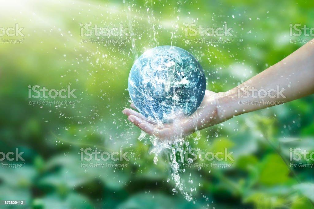 Agua que vierte en el planeta tierra a mano para ahorrar recursos y cura la campaña mundial, temas de medio ambiente, elementos de esta imagen proporcionada por la NASA. - foto de stock