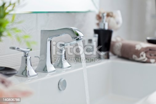 Water pouring out of modern bathroom faucet