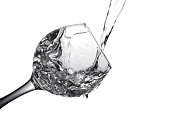 Colorless liquid, water,vodka is poured into a glass, liquid in a speaker, isolated on a white background