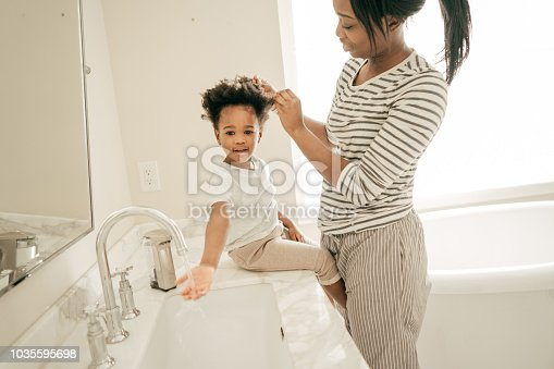 A child is playing with water while her mom is busy.