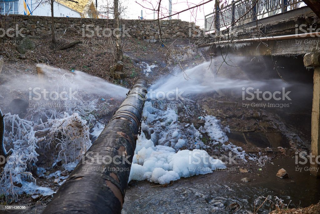Water pressure from a large pipe over the river Water pressure from a large pipe over the river, in winter Air Valve Stock Photo
