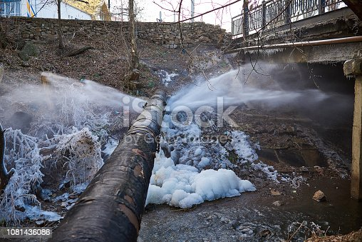 Water pressure from a large pipe over the river, in winter