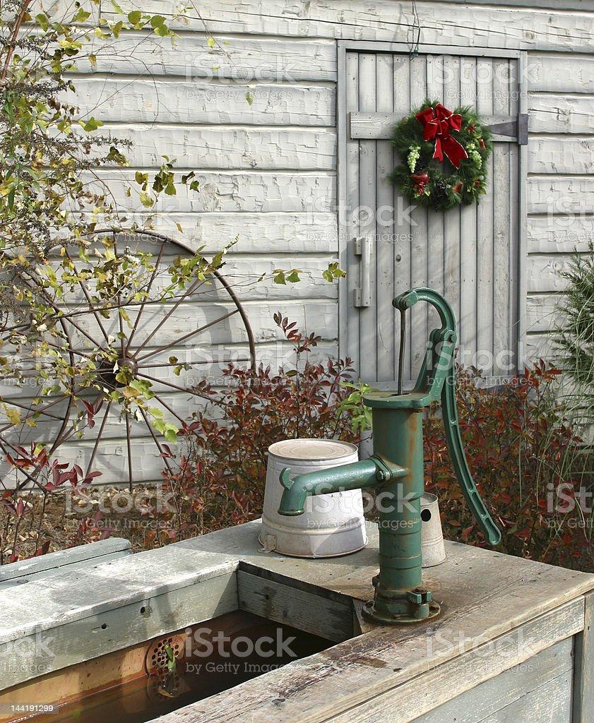 Water Pump, Christmas Wreath on White Barn Door stock photo