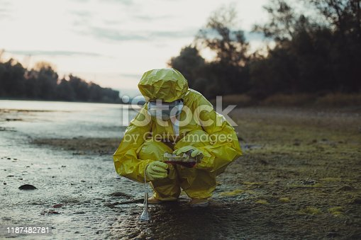 Scientist examing toxic water, side view