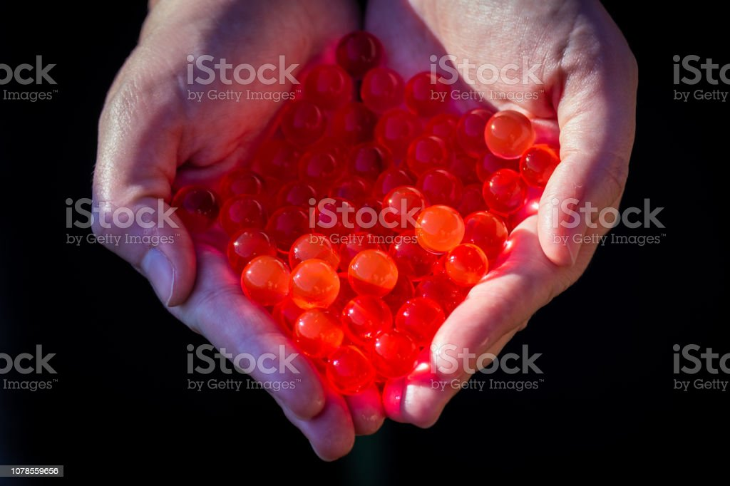 Water red gel balls. Small gel ball in the hand. Polymer gel. Silica...