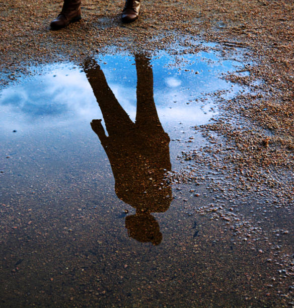 water reflection of a persons silhouette with the vibrant sky - deign stock pictures, royalty-free photos & images