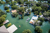 Water Rescue crew on site searching for survivors after dangerous Flooding Aerial drone views high above Flooding caused by Climate Change leaving entire neighborhood underwater and houses completely under water , boat with water rescue searching for people stuck in their flooded homes