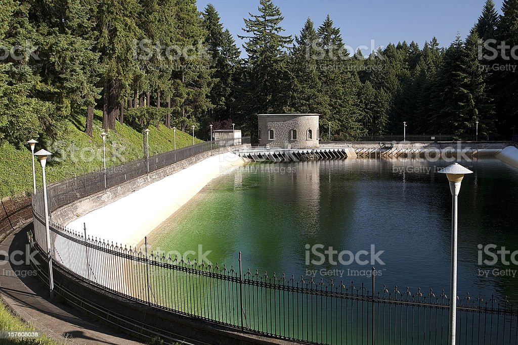 Water reservoir in green forest surrounded by fence and path stock photo